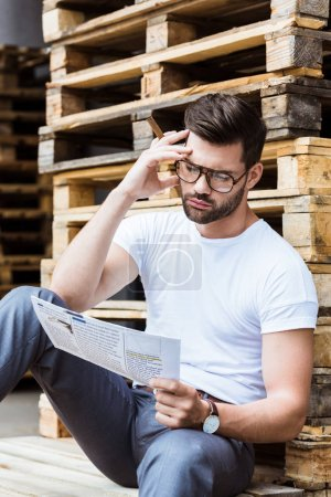 Fashionable confident businessman in glasses smoking cigar while reading business document by wooden palettes