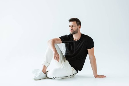 Handsome bearded man in casual clothes sitting on floor on white background