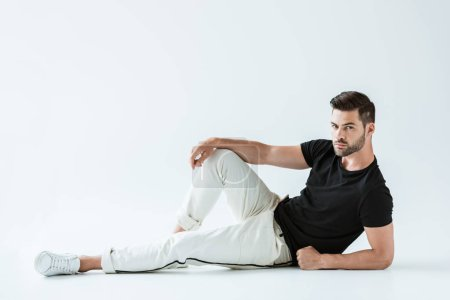 Photo for Stylish young man in casual clothes sitting on floor on white background - Royalty Free Image