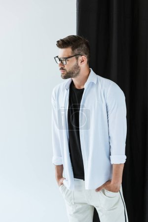 Fashionable confident man wearing glasses and white shirt standing by black curtain