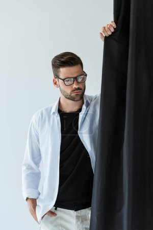 Handsome bearded man wearing glasses and white shirt standing by black curtain