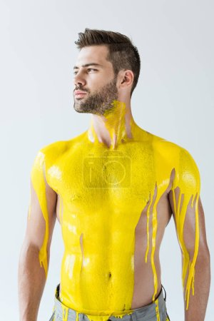 Photo for Young man covered with yellow paint isolated on white background - Royalty Free Image