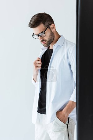 Thoughtful bearded man in glasses standing by black curtain
