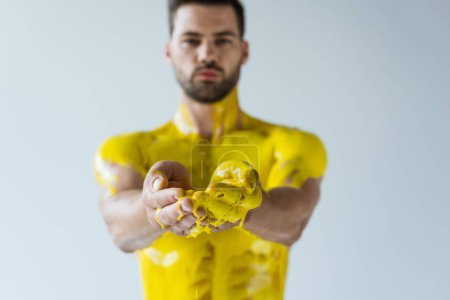 Selective focus of man showing hands in yellow paint isolated on white background