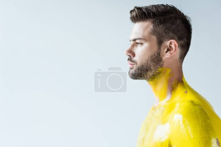 Young man with body painted in yellow isolated on white background