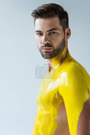 Handsome bearded man with body covered in yellow liquid isolated on white background