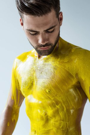 Man looking at his body painted yellow isolated on white background