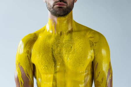 Male body stained with yellow paint isolated on white background