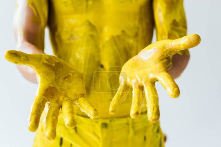 Cropped view of male hands and body in yellow paint isolated on white background