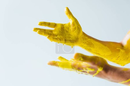 Cropped view of male hands covered with yellow paint isolated on white background