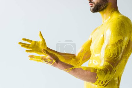 Handsome bearded man stained with yellow liquid isolated on white background