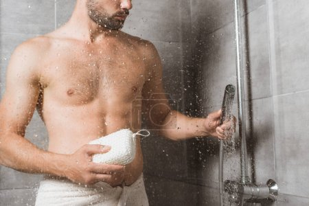 Handsome bearded man holding sponge behind shower glass