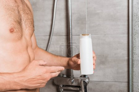 Photo pour Cropped view of muscular man holding washing gel in shower - image libre de droit