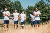 multicultural group of soldiers running on range on summer day