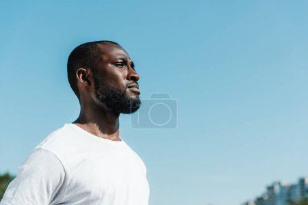 side view of confident african american soldier in white shirt against blue sky