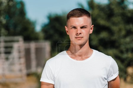 portrait of young soldier in white shirt looking at camera on range
