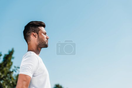 side view of young soldier in white shirt against blue sky
