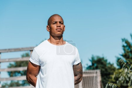 portrait of african american tattooed soldier in white shirt standing on range
