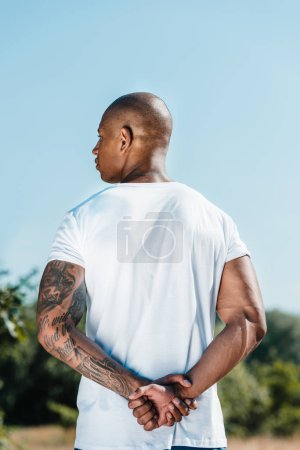 back view of african american tattooed soldier in white shirt against blue sky