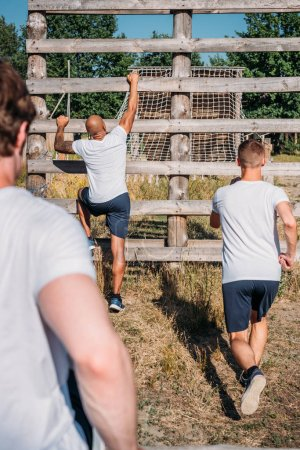 back view of multicultural soldiers practicing obstacle run on range on summer day