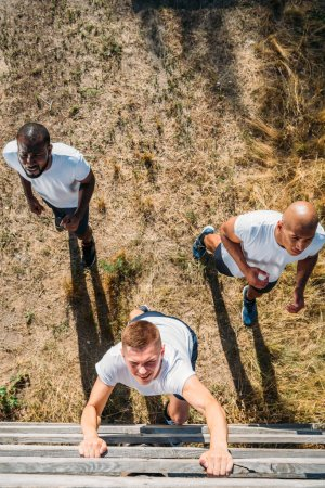 overhead view of multiethnic soldiers practicing in obstacle run on range
