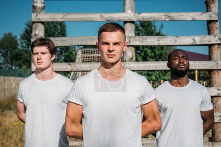 portrait of interracial young soldiers in white shirts on range