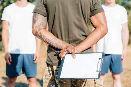 cropped shot of african american tactical instructor with notepad and soldiers on range