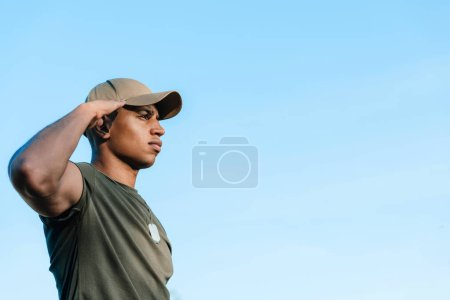 side view of african american soldier in cap with tag dog against blue sky