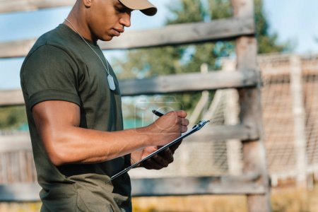 side view of african american tactical instructor making notes in notepad on range
