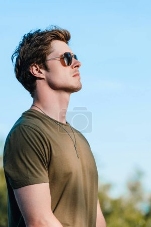 side view of confident soldier in sunglasses against blue sky