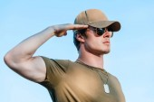 side view of young soldier in cap and sunglasses against blue sky