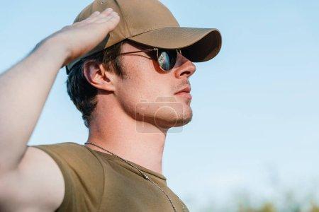Photo pour Vue latérale du jeune soldat en casquette et lunettes de soleil contre le ciel bleu - image libre de droit