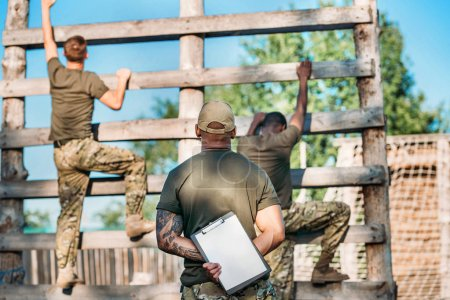 Photo for Selective focus of tactical instructor with notepad examining multiracial soldiers during obstacle run on range - Royalty Free Image