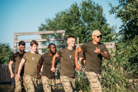 multiethnic soldiers in military uniform running on range