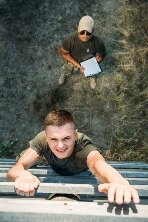 overhead view of african american tactical instructor with notepad examining young soldier during obstacle run