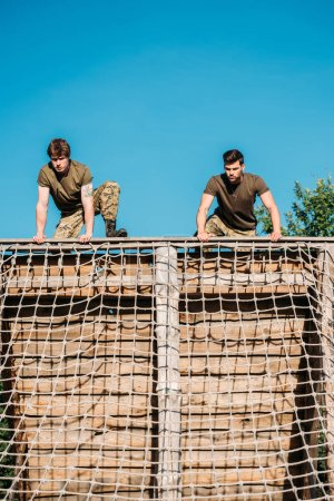 low angle view of young soldiers practicing during obstacle run on range