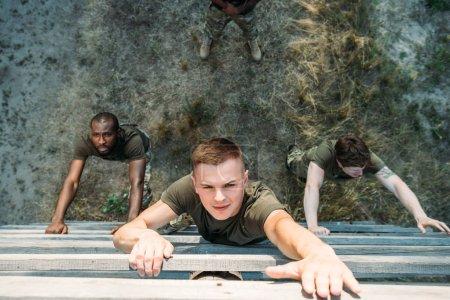 Photo pour Vue aérienne de multiethniques soldats pratiquant en obstacle courir sur la plage - image libre de droit