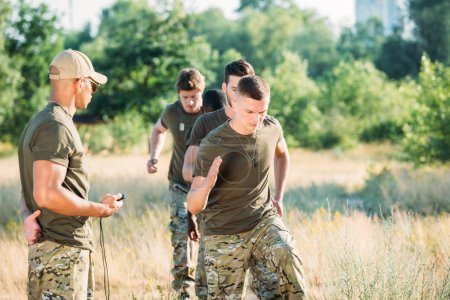 tactical instructor with stop watch examining multiracial soldiers during obstacle run on range