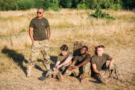 Photo pour Jeunes soldats multiraciaux en uniforme militaire reposant sur le champ de tir - image libre de droit