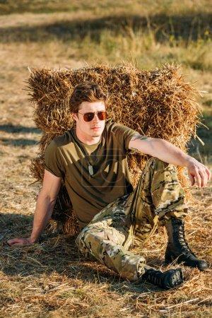 Photo pour Jeune soldat en uniforme militaire et lunettes de soleil reposant près du foin sur le champ de tir - image libre de droit