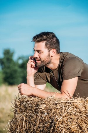 smiling soldier in military uniform talking on smartphone while leaning on hay on range