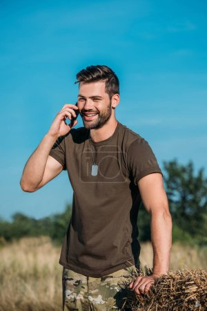 smiling soldier in military uniform talking on smartphone on range