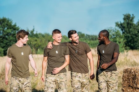 portrait of multicultural smiling soldiers in military uniform on range on summer day