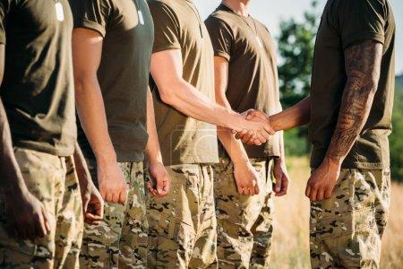 Photo pour Vue partielle du soldat et de l'instructeur tactique en uniforme militaire serrant la main à portée - image libre de droit