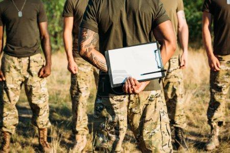 Photo pour Vue partielle de l'instructeur tactique avec bloc-notes et soldats multiraciaux en uniforme militaire à portée - image libre de droit