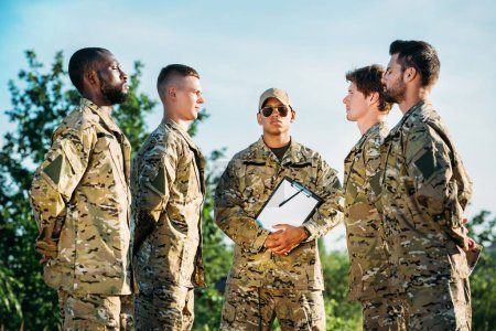 african american tactical instructor with notepad and young interracial soldiers in military uniform on range