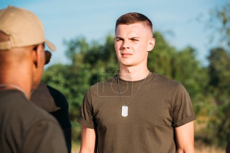 selective focus of young soldier with tag dog on range
