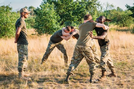 multiracial soldiers in military uniform practicing hand to hand fighting on range