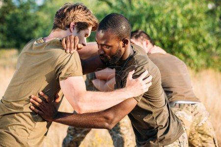Photo pour Soldats multiraciaux en uniforme militaire pratiquant le combat au corps à corps à portée - image libre de droit
