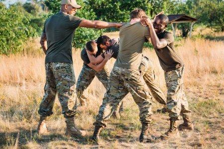 Photo pour Multiraciales soldats vêtus d'uniformes militaires pratiquant combats corps à corps sur la plage - image libre de droit